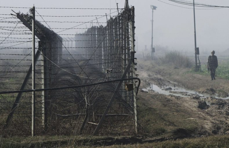 An Indian BSF soldier patrols near the fenced border with Pakistan amid fog in Suchetgarh